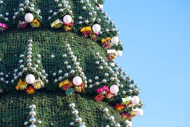 Árvore de natal decorada na superfície do céu azul. parte de uma grande árvore de natal ao ar livre, close up