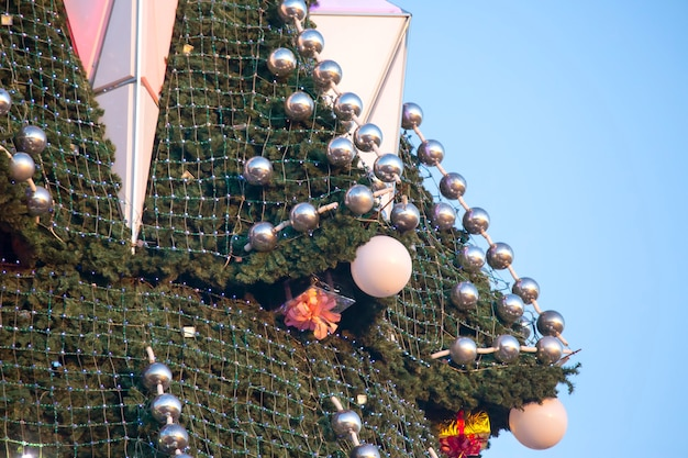 Árvore de natal decorada no fundo do céu azul. parte de uma grande árvore de natal ao ar livre, close-up