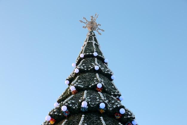 Árvore de natal decorada no fundo do céu azul