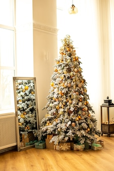Árvore de natal decorada no quarto. perto de uma caixa diferente com presentes no ano novo