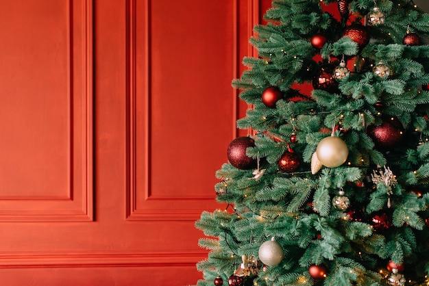 Árvore de natal decorada perto da parede vermelha, close-up