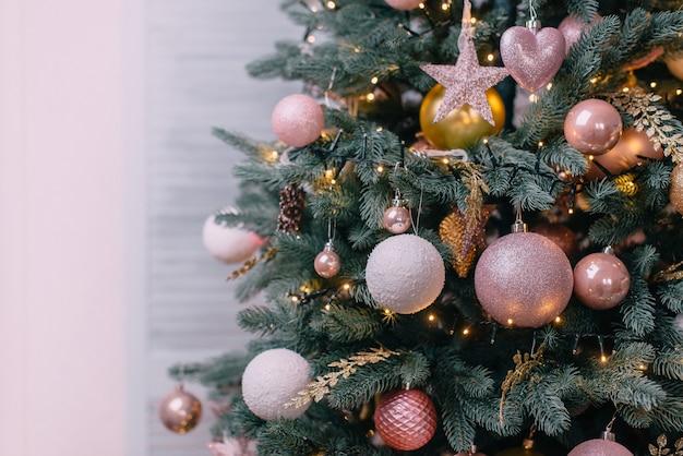 Árvore de natal decorada perto de uma parede branca, close-up