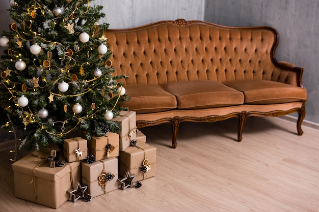 Árvore de natal decorada, pilha de caixas de presente e espaço de cópia sobre o piso de madeira
