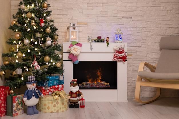 Árvore de natal decorada, presentes em caixas, uma estatueta de papai noel, uma lareira acesa. ano novo, natal. foco seletivo.