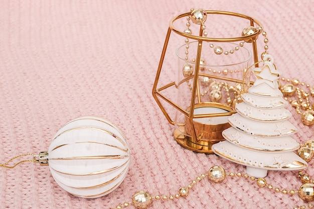 Árvore de natal decorativa, castiçal de ouro, bugiganga e guirlanda de ouro sobre fundo de malha rosa.