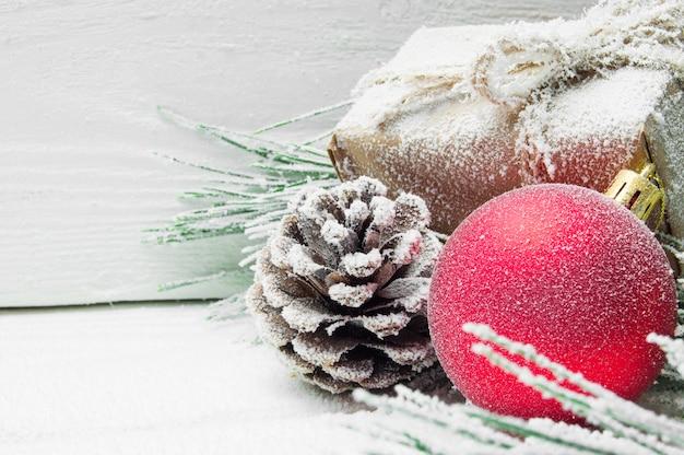 Árvore de natal do ramo nevado e bola de cone e vermelho com caixa de presente na superfície vintage de madeira branca