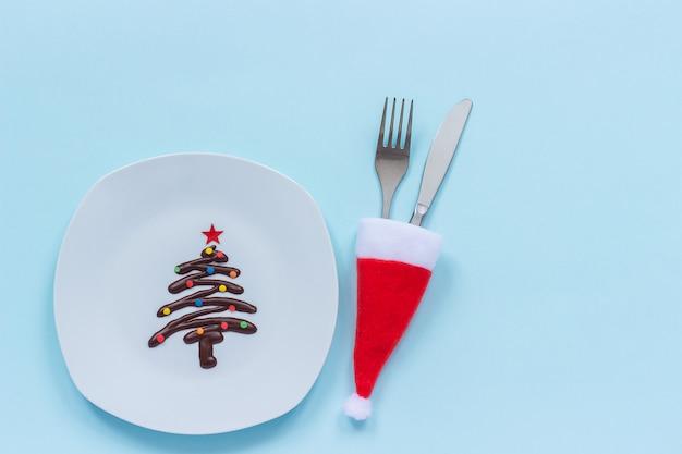 Árvore de natal doce de chocolate no prato e talheres