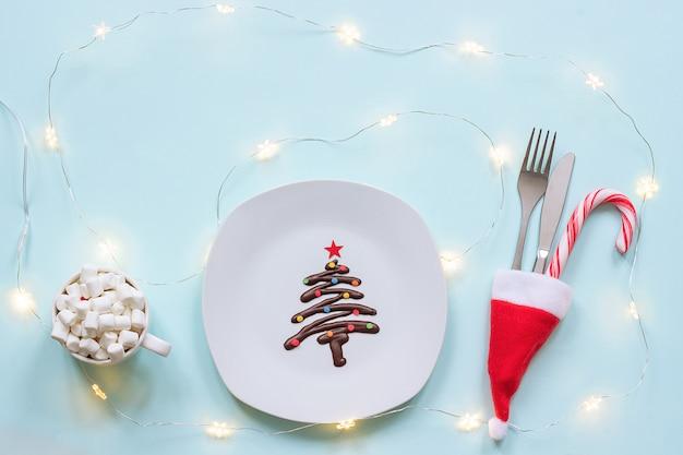 Árvore de natal doce feita de chocolate, talheres e xícara de marshmallow de cacau e guirlanda de lâmpadas