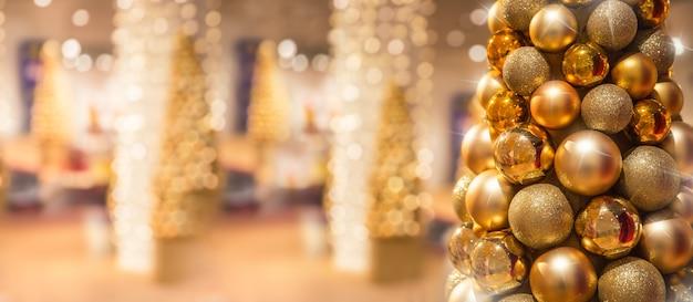 Árvore de natal dourada com bolas em shopping center de luxo.