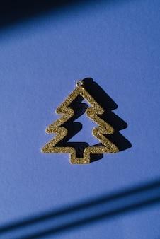 Árvore de natal dourada decorativa com uma sombra dura sobre um fundo azul. cartão de natal criativo