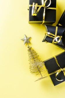Árvore de natal dourada e presentes em fundo amarelo
