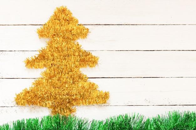 Árvore de natal dourada na parede branca