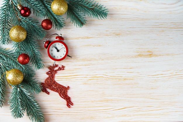 Árvore de natal e ano novo decorada, cervo de brinquedo e relógio em fundo branco de madeira