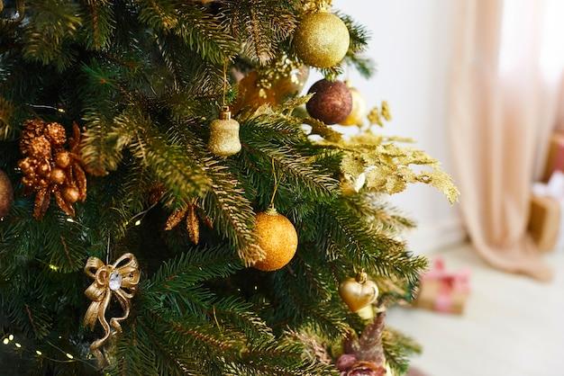 Árvore de natal e ano novo decorada com brinquedos de ouro. quarto decorado de férias