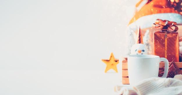 Árvore de natal e caixa de presente na caneca com bokeh de fundo claro festival
