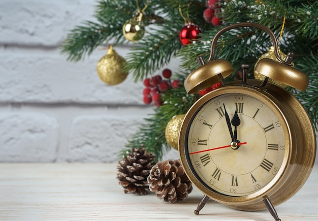 Árvore de natal e contagem regressiva para o ano novo. relógio retrô de bronze, cone, bolas e ramos de abeto de pinheiro em fundo de tijolo branco com espaço de cópia
