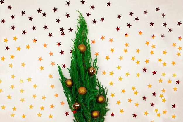 Árvore de natal e decorações de ouro em um fundo branco.