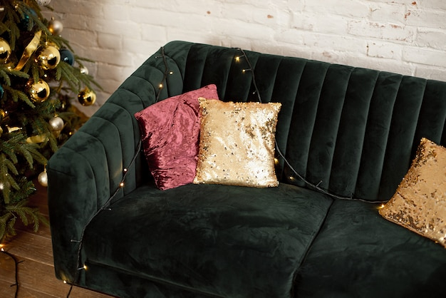 Árvore de natal e um sofá verde com almofadas