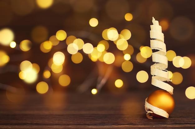 Árvore de natal e uma bola em uma mesa de madeira na frente do bokeh dourado
