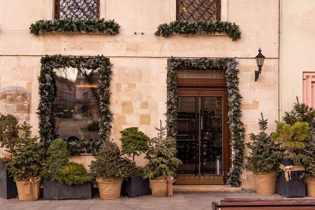 Árvore de natal elegante com bagas vermelhas, grinalda nas portas e trenó de madeira na frente da loja no mercado de férias na rua da cidade. decoração de rua de natal. espaço para texto. decoração rústica.