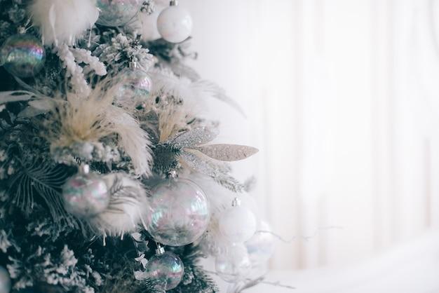 Árvore de natal em close-up decorada com bolas prateadas em fundo branco
