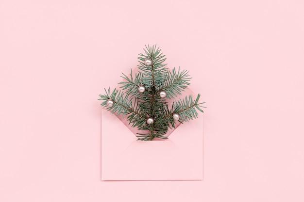 Árvore de natal em envelope com pérolas na superfície rosa