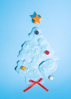 Árvore de natal em forma de gelo derretido sobre um fundo azul. vista do topo.