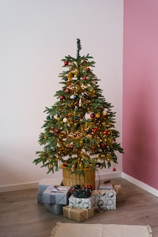 Árvore de natal em luzes com brinquedos e presentes debaixo dela no interior da sala de estar