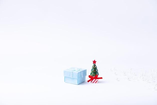 Árvore de natal em miniatura, caixa de presente e contas de pérolas em um fundo branco. ano novo e natal. close-up, banner.