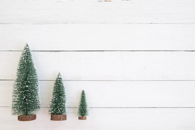 Árvore de natal em miniatura, decoração de natal e ornamento em fundo branco de madeira. estilo vintage. vista do topo.