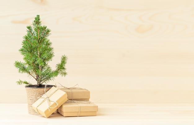 Árvore de natal em vaso com caixas de presente ecológicas em fundo de madeira