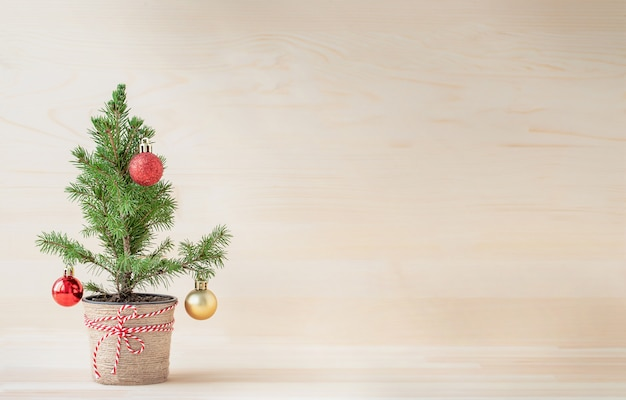 Árvore de natal em vaso de flores com enfeites de natal em fundo de madeira