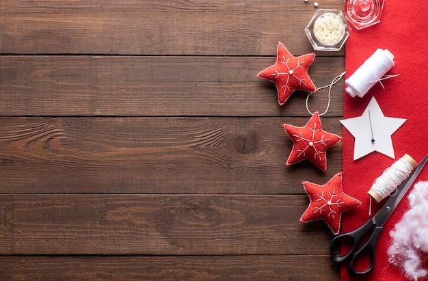 Árvore de natal, enfeites de estrela de brinquedo, fios vermelhos e brancos, agulha, padrão de papel, feltro na madeira