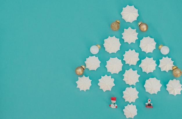 Árvore de natal feita com merengues brancos com bolas de natal e enfeites de natal de madeira