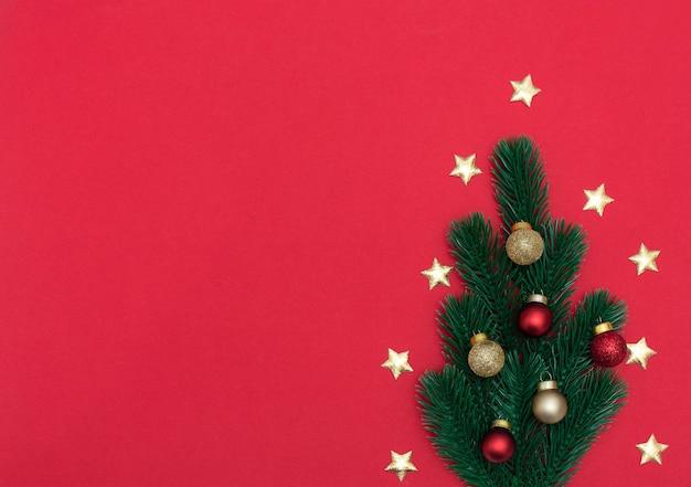 Árvore de natal feita de abeto com decorações de natal em fundo vermelho.