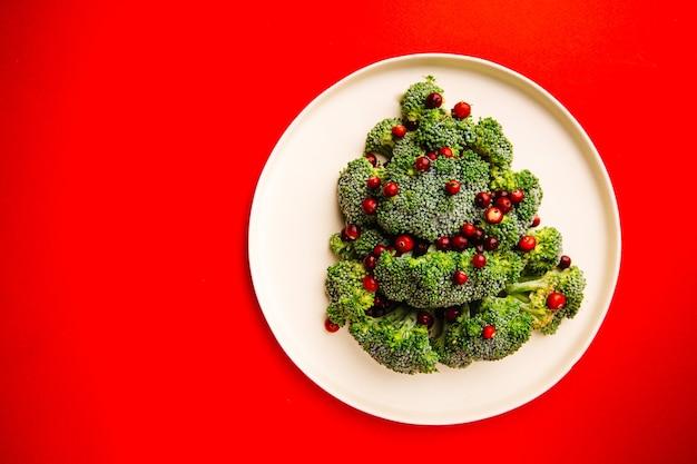 Árvore de natal feita de brócolis e cranberry na chapa branca e vista superior com fundo vermelho