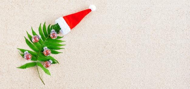 Árvore de natal feita de brunch de planta tropical verde com pequenas decorações de natal vermelhas na areia