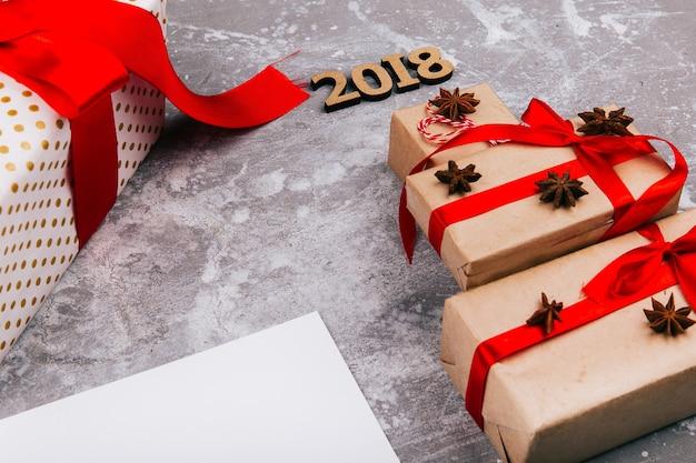 Árvore de natal feita de caixas de presente vermelho e número 2018 sobre ela fica no chão cinza sobre cartão branco vazio