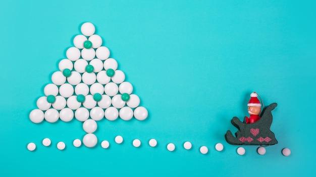 Árvore de natal feita de comprimidos em um fundo azul. ano novo na medicina, farmácia e drogaria.
