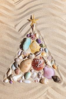 Árvore de natal feita de conchas e corais na areia da praia, decoração festiva