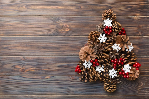 Árvore de natal feita de cones naturais em fundo colorido, vista de cima. conceito mínimo de ano novo com espaço de cópia