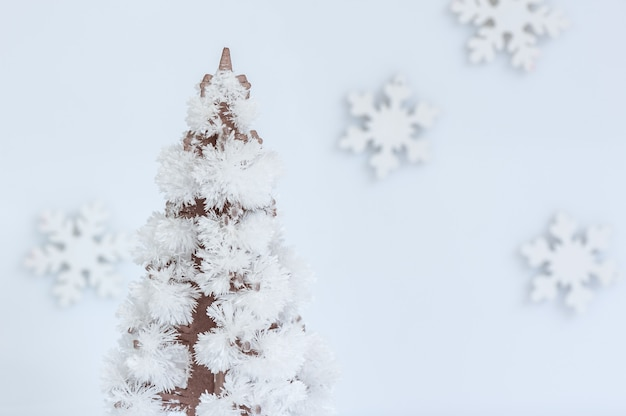 Árvore de natal feita de cristais em fundo branco com flocos de neve