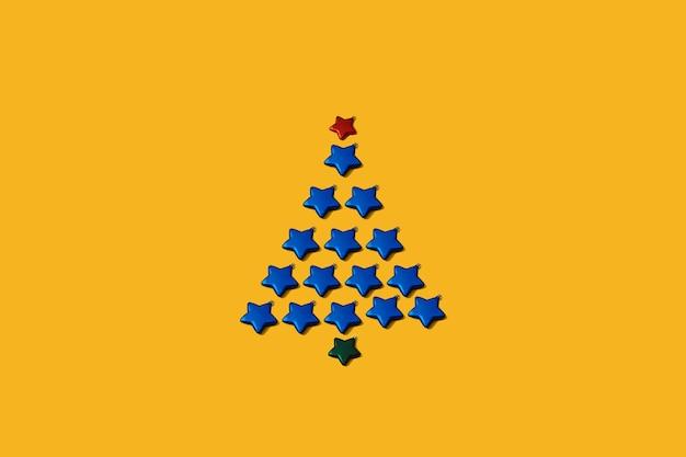 Árvore de natal feita de decoração de bugigangas em forma de estrela azul. conceito mínimo de ano novo em um fundo amarelo. cartão de férias ou padrão de papel de parede. espirito natalino.