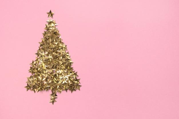 Árvore de natal feita de estrelas douradas glitter confetes em fundo rosa. cenário de férias de natal.