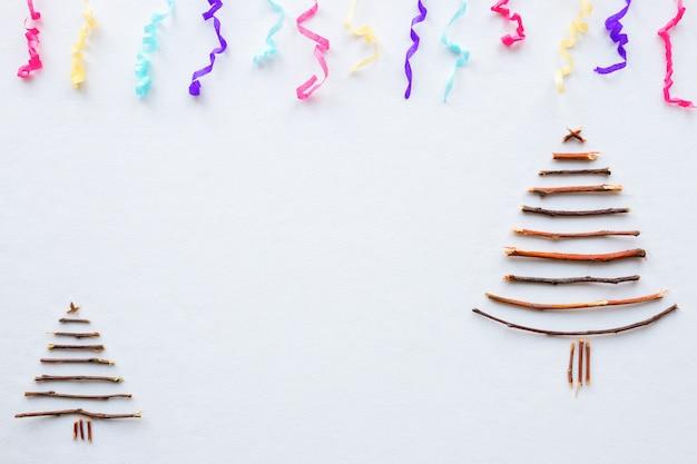 Árvore de natal feita de galhos em um fundo branco com confete