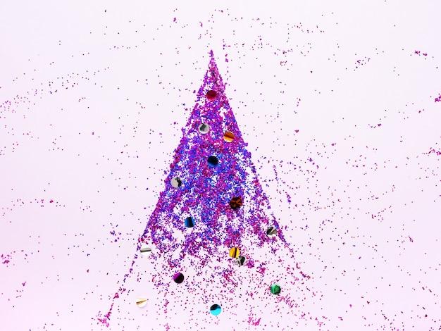 Árvore de natal feita de lantejoulas rosa brilhante em um fundo rosa, vista plana leiga, superior. conceito minimalista de ano novo. plano de fundo ou cartão de natal.