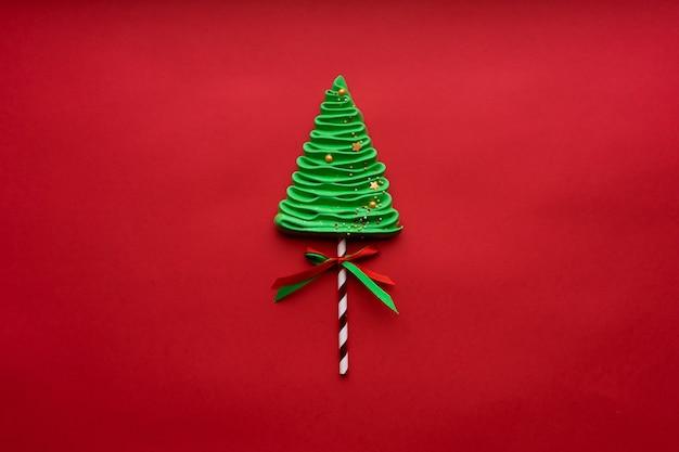 Árvore de natal feita de merengues no estilo de ano novo em um fundo vermelho. localização no meio.