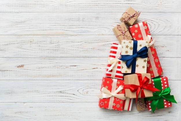 Árvore de natal feita de presentes lindamente embrulhados em fundo colorido, vista de cima. conceito mínimo de caixa de presente de ano novo com espaço de cópia