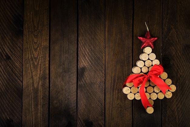 Árvore de natal feita de rolhas de vinho sobre fundo de madeira. cartão postal de maquete com árvore de natal e cópia espaço para texto. vista do topo.