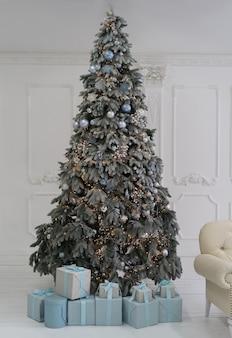 Árvore de natal iluminada com presentes embaixo contra uma parede vintage branca